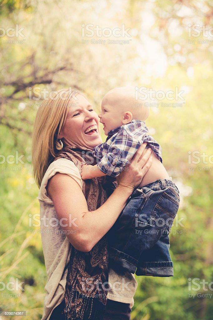 Joyful Mother Lifting Baby Boy - Outdoors Nature Summer Sunshine stock photo