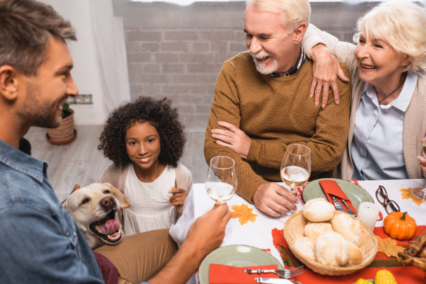 joyful multicultural family holding glasses of white wine while celebrating thanksgiving near golden retriever joyful multicultural family holding glasses of white wine while celebrating thanksgiving near golden retriever thanksgiving pets stock pictures, royalty-free photos & images