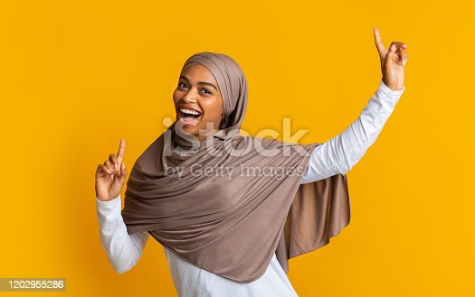 Live With Fun. Joyful black muslim woman in hijab dancing and singing with raised index fingers over yellow background, empty space