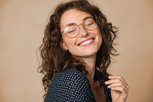 Casual cheerful woman with eyeglasses smiling at camera on cream background. Close up of happy young woman laughing with eyeglasses. Beautiful natural girl having fun with closed eyes showing a big grin.