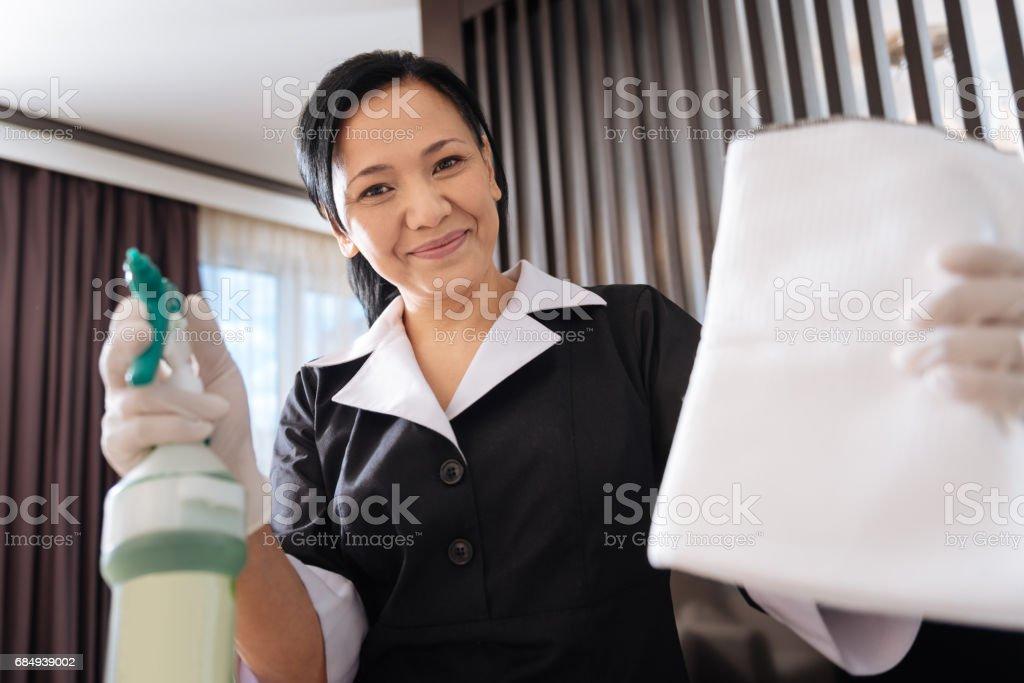 Freudige nette Zimmermädchen zeigt Ihnen ihr equipment Lizenzfreies stock-foto