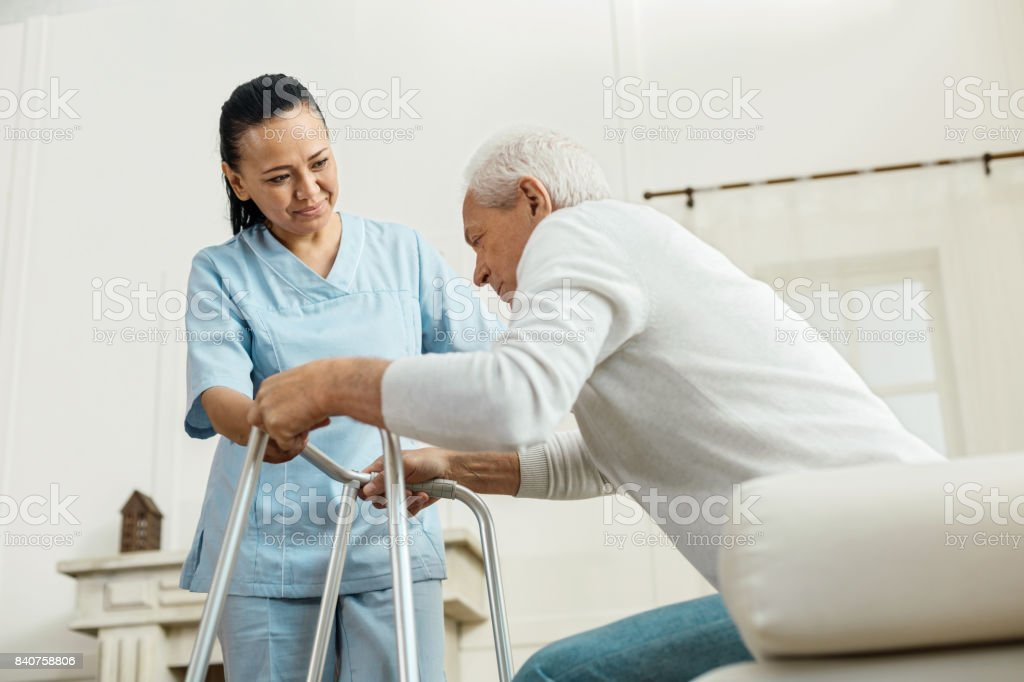 Joyful nice woman helping an elderly man stock photo