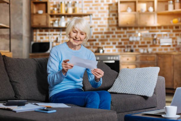 joyful nice woman reading a note - social security check stock photos and pictures