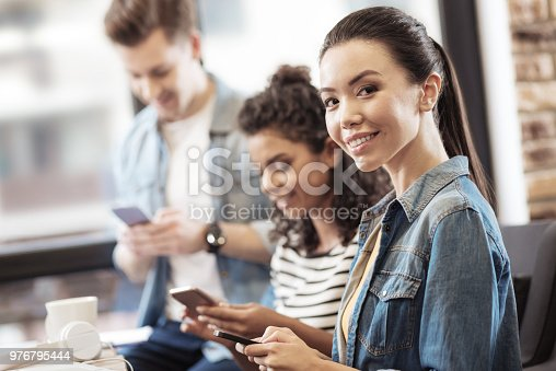 Social networking. Joyful nice woman smiling while typing a message on her smartphone