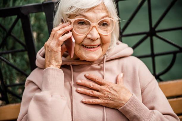 Joyful old lady talking on cell phone outdoors stock photo stock photo