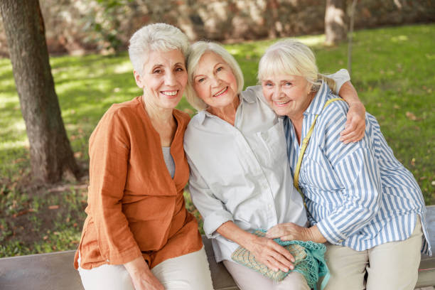 Joyful old women sitting on bench in the park stock photo