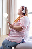 Joyful overweight young woman listening to music