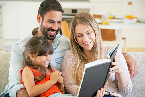 Joyful parents couple and little black haired girl sitting on couch in living room, reading book together and laughing. Childhood or literature concept
