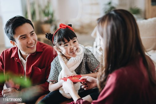 Joyful parents giving red envelops (lai see) to their daughter and she receives them with both hands