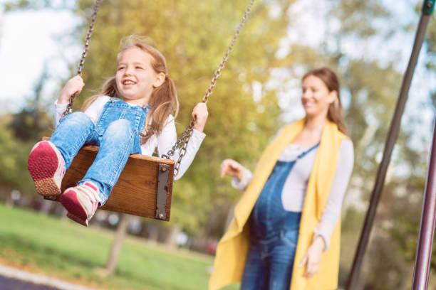 fröhlichen spielen im park mit mutter - latzhose für schwangere stock-fotos und bilder