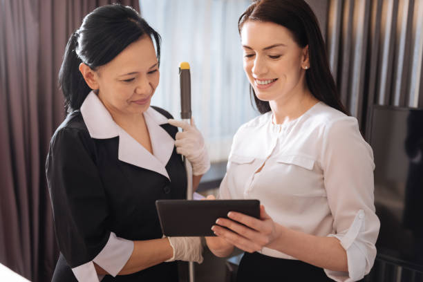 joyful pleasant women looking at the tablet screen - maid stock pictures, royalty-free photos & images