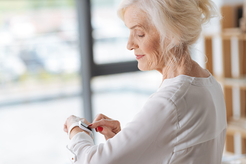 Joyful positive woman using a smartwatch