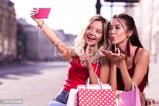 Best selfie. Joyful positive women posing for a photo while standing on the street
