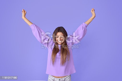 istock Joyful pretty young woman stretching arms 1181317190