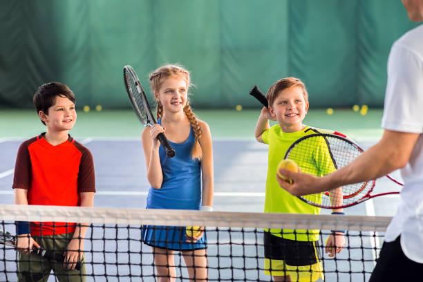 alegría alumnos aprendiendo a jugar al tenis - tenis fotografías e imágenes de stock