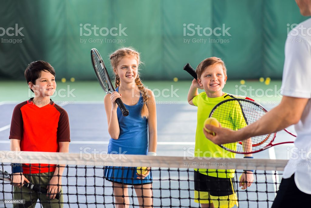 Joyful pupils learning to play tennis stock photo