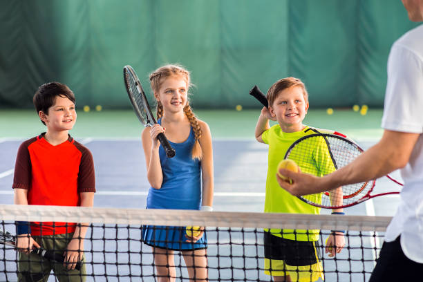 joyful pupils learning to play tennis - tennis stock pictures, royalty-free photos & images
