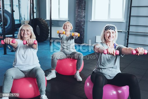 936573360 istock photo Joyful retired ladies lifting dumbbells at gym 936575770