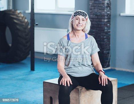 936573360istockphoto Joyful retired lady resting on wooden box in fitness club 936572676