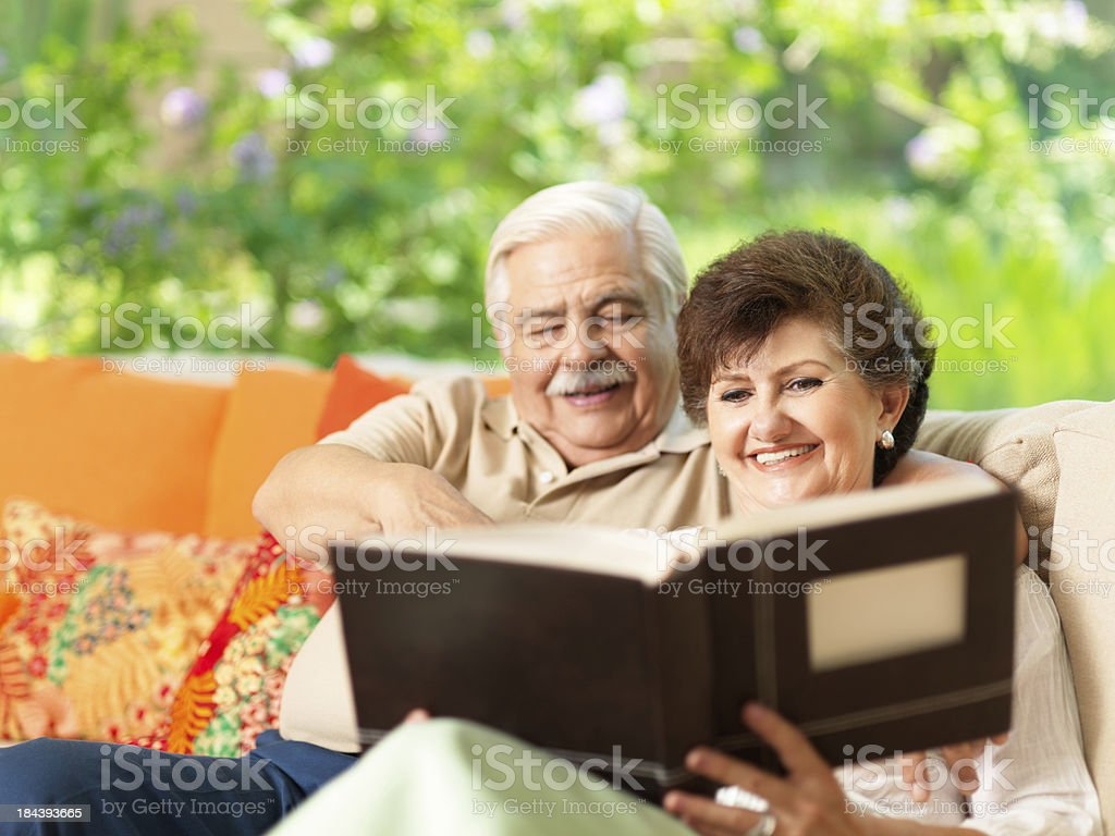 Joyful senior couple looking at their photo album royalty-free stock photo