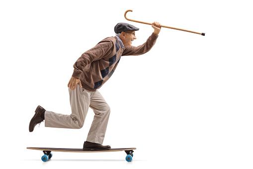 Full length profile shot of a joyful senior holding a cane and riding a longboard isolated on white background
