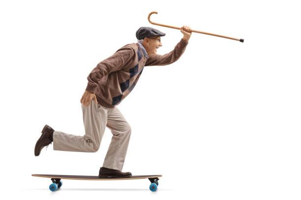 fröhliche senioren hält einen stock und reiten eine longboard - 70 jahre kleidung stock-fotos und bilder