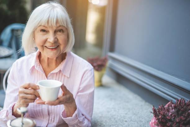 neşeli kıdemli bayan açık havada sıcak içecek - yaşlı kadınlar stok fotoğraflar ve resimler