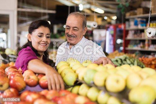 istock Joyful senior latin couple buying apples at supermarket 587200428