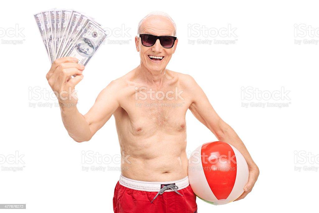1f120e3b9416 Allegro uomo anziano con soldi e un pallone da spiaggia foto stock  royalty-free