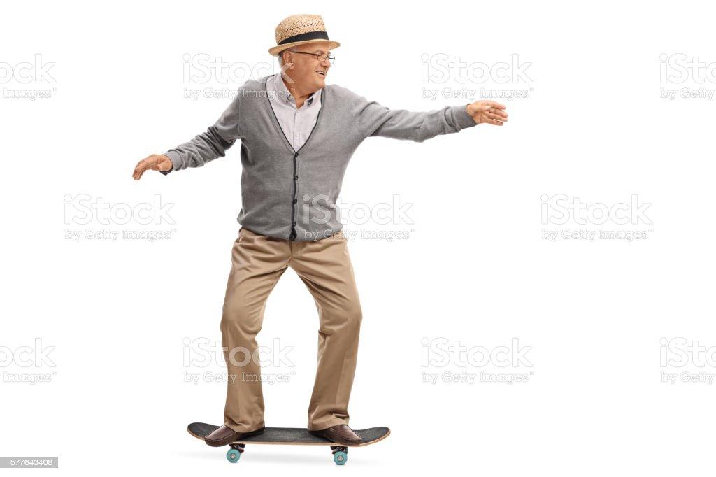 Joyful senior man riding a skateboard stock photo