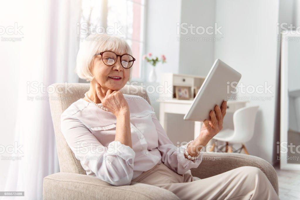 Freudige senior Frau liest aus Tablet im Wohnzimmer – Foto