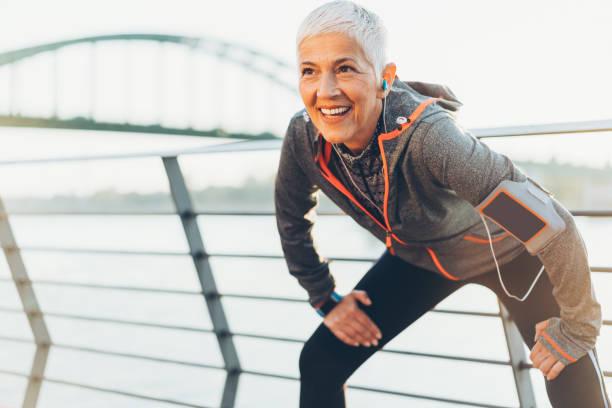 vreugdevolle senior vrouw stretching - atlete stockfoto's en -beelden