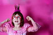 Happy small princess girl in pink dress and crown with glasses isolated on pink background.