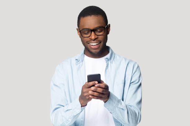 Fröhlich lächelnden afrikanischen amerikanischen jungen Mann spielen Online-Spiel. – Foto