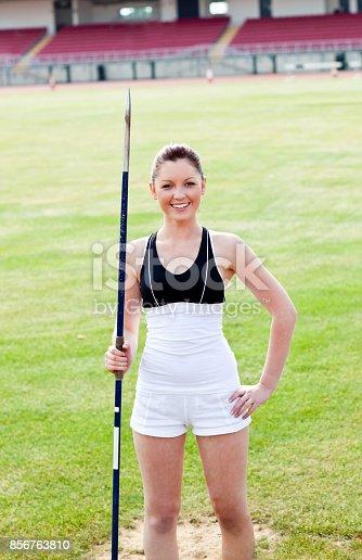 856713554istockphoto Joyful sporty woman holding a javelin standing in a stadium 856763810