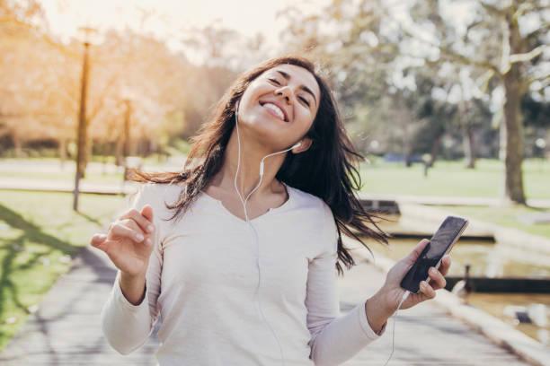Fröhliche Schülermädchen in Ohrhörern mit Smartphone und Tanz – Foto