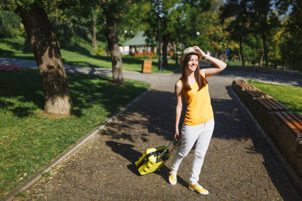 Joyful traveler tourist woman in yellow summer casual clothes with suitcase keeping hand near hat, walk in city outdoor. Girl traveling abroad to travel on weekends getaway. Tourism journey lifestyle. stock photo