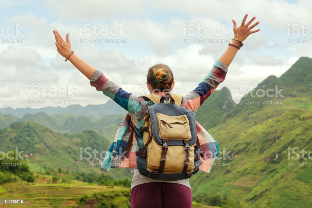 joyful traveller jumping with raised hands enjoying view at mountains stock photo