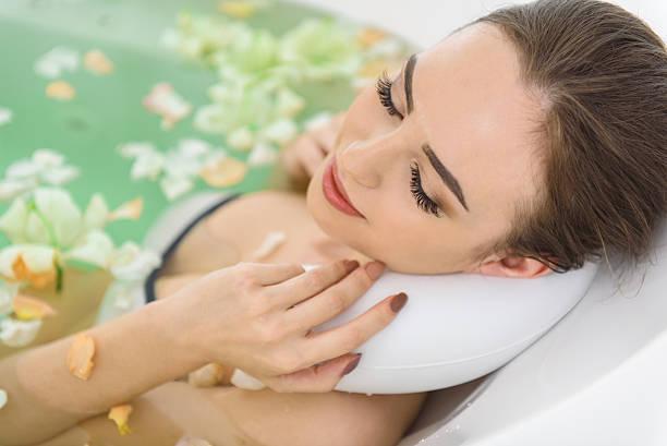 joyful woman bathing in water at spa - badewannenkissen stock-fotos und bilder