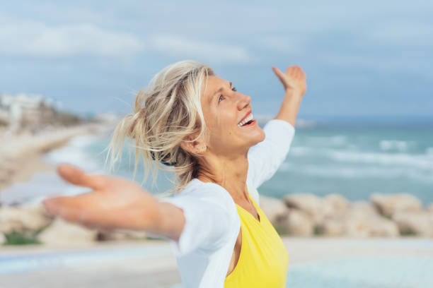 Joyful woman enjoying the freedom of the beach Joyful woman enjoying the freedom of the beach standing with open arms and a happy smile looking up towards the sky freedom stock pictures, royalty-free photos & images