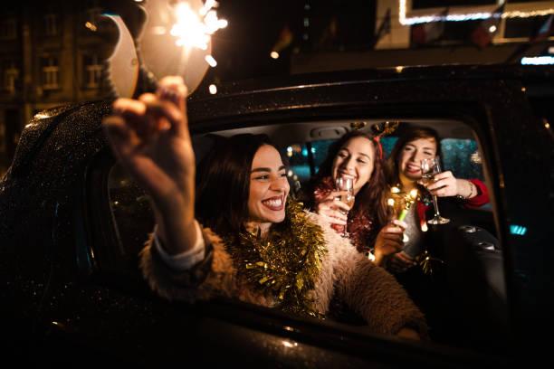 Joyful woman holding sparkler while celebrating New Year stock photo