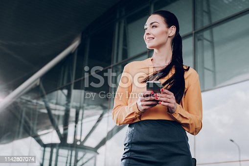 Positive expectation. Beautiful lady is standing near the entrance and waiting with smartphone. Copy space in left side