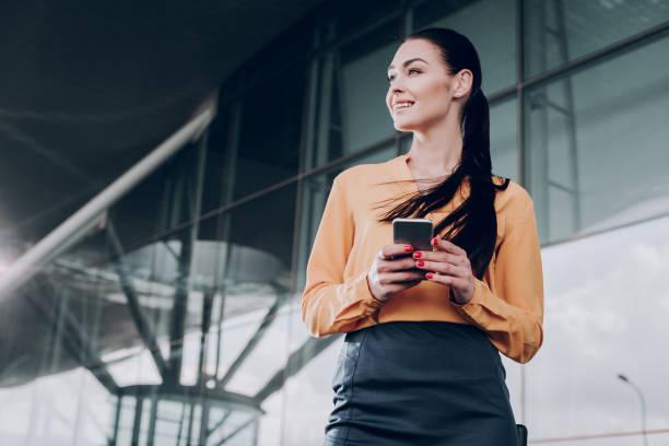 vrolijke vrouw houdt mobiele telefoon buiten - business woman phone stockfoto's en -beelden