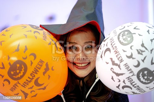 Joyful woman playfully posing in halloween. Beautiful young surprised woman in witches hat and short dress holding white and orange air balloons.