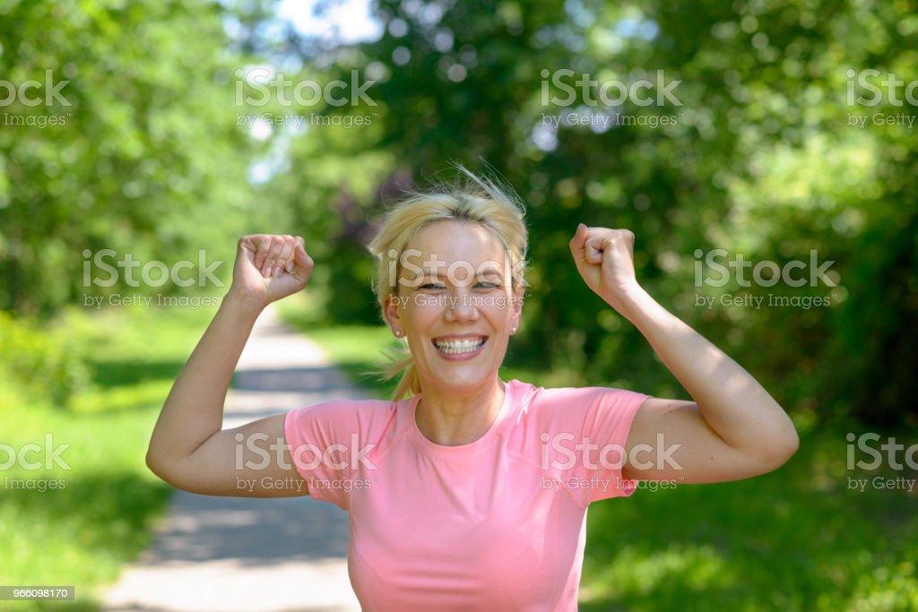 Glada kvinna kör längs ett spår du skogsmark - Royaltyfri Aktiv livsstil Bildbanksbilder