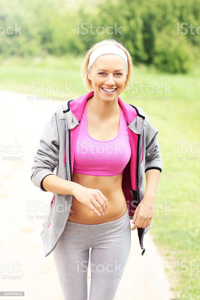 Joyful woman running in the park stock photo