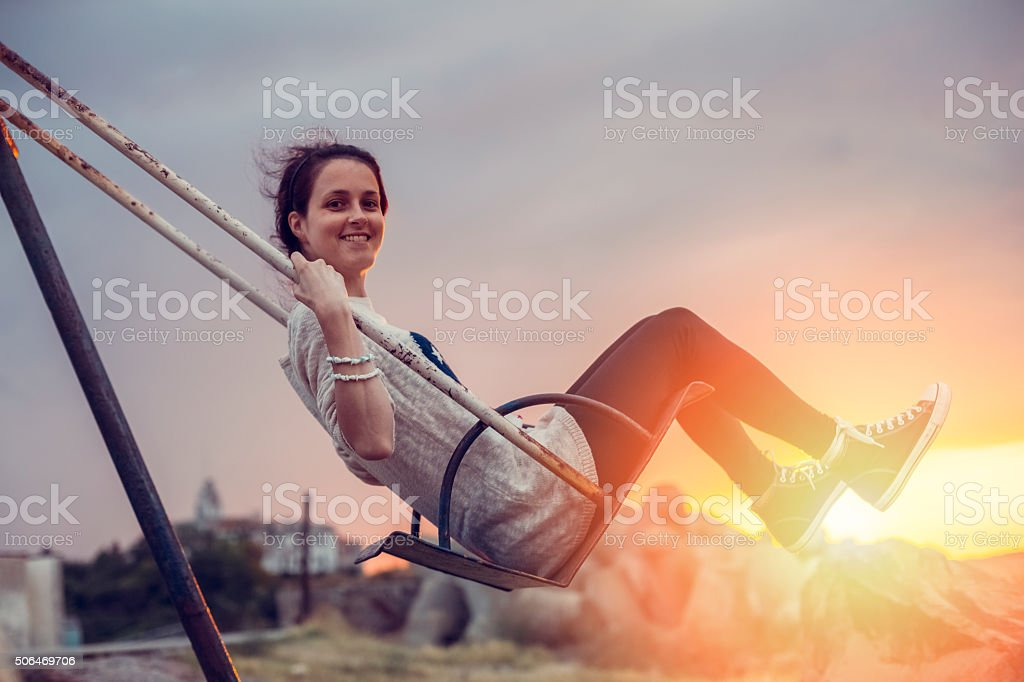 Joyful woman swinging at sunset stock photo