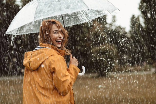 Joyful woman walking in rainy weather stock photo