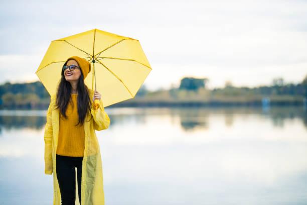 fröhliche frau bei regnerischem wetter - regenzeit stock-fotos und bilder