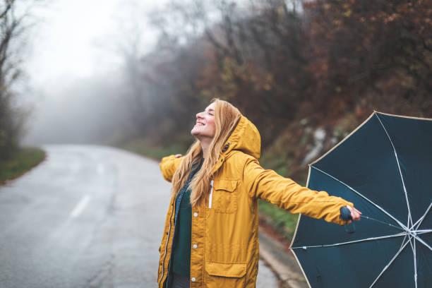 Joyful woman walking in rainy weather stock photo